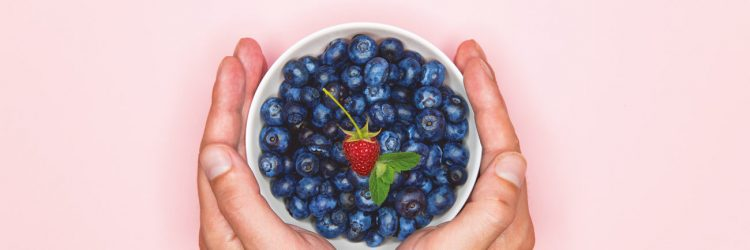 blueberries in the hand. Blueberries in hands on a colored background. place for writing. view from above